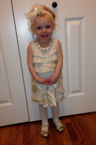 Modeling her Gatsby hairpiece, glitz pearls, and flowergirl dress!